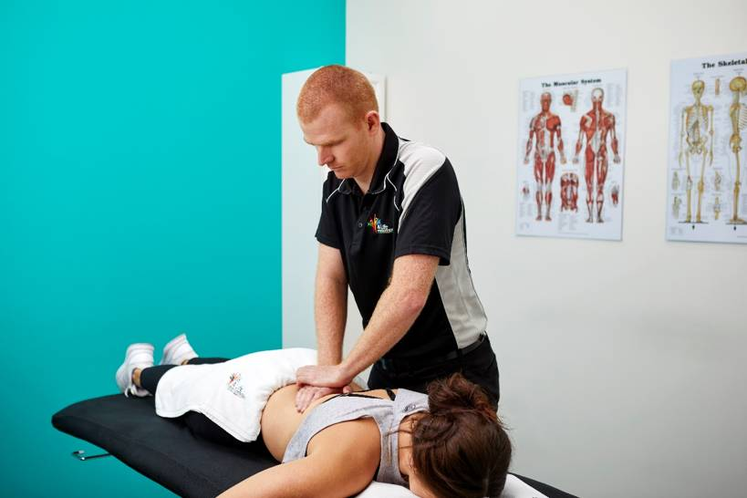 Physiotherapist applying a technique to a patients back.